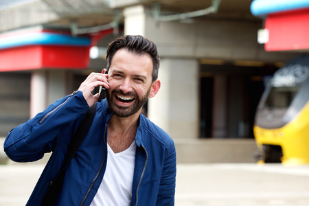 waiting phone call: Close up portrait of handsome mature man talking on mobile phone at railway station and laughing