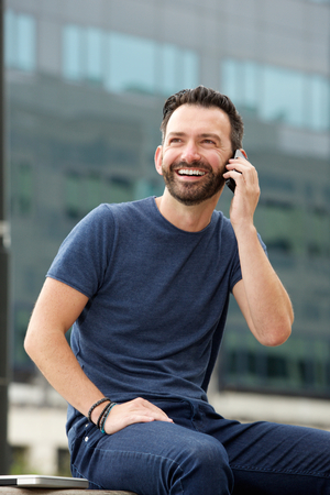 mature man: Portrait of happy mature man sitting outdoors and talking on mobile phone