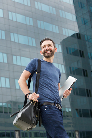 man with laptop: Portrait of happy man walking outdoors with handbag and laptop Stock Photo
