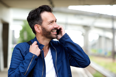 waiting phone call: Close up portrait of cheerful mature man standing outdoors and talking on mobile phone