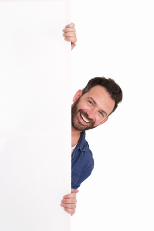 Portrait of smiling mature man peeking over blank poster sign against white background Stock Photo