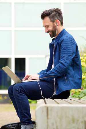 Side portrait of mature man wearing earphones sitting outdoors and working on laptop.