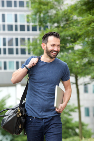 man with laptop: Portrait of cheerful middle aged guy walking outdoors with handbag and laptop