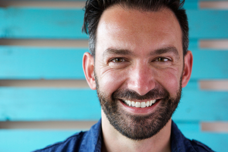 Close up portrait of handsome mature man with beard smiling Stock Photo