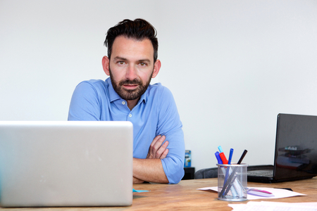 hombres trabajando: Portrait of handsome mature business man sitting at his desk with laptop