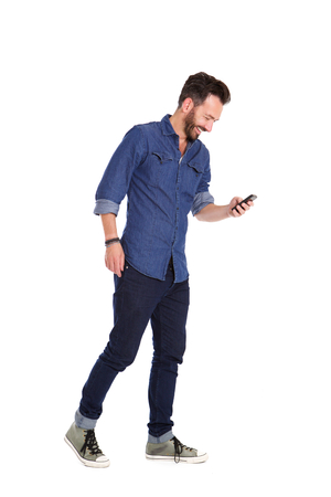 Full body portrait of smiling mature man walking and using mobile phone over white background
