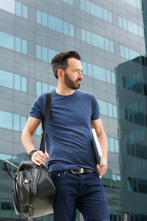 man with laptop: Portrait of guy standing outdoors with handbag and laptop looking away