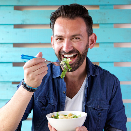 Close up portrait of cheerful man eating salad from bowl