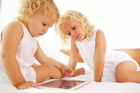 niños sentados: Retrato de las hermanas que se sientan en cama y que usa la tableta digital de