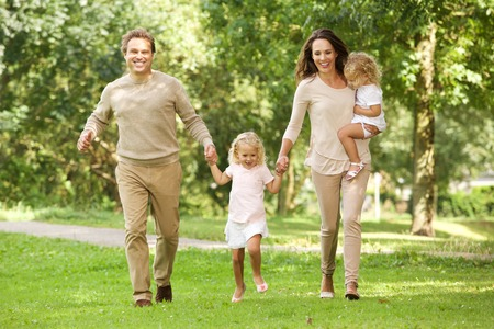 Portrait of happy young family of four walking together in the park
