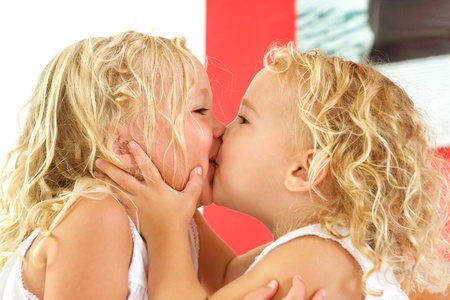 girls kissing girls: Close up portrait of cute little girls kissing each other at home