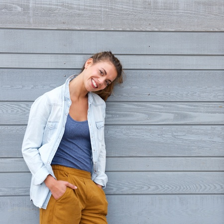 confident woman: Portrait of smiling confident woman leaning against wall Stock Photo
