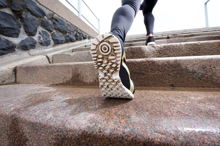 shoe model: Low angle rear portrait of female runner in action on staircase Stock Photo