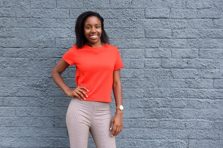 enjoying life: Portrait of young happy african woman standing against gray wall.