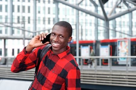black train: Portrait of cheerful young african guy using cell phone at train station