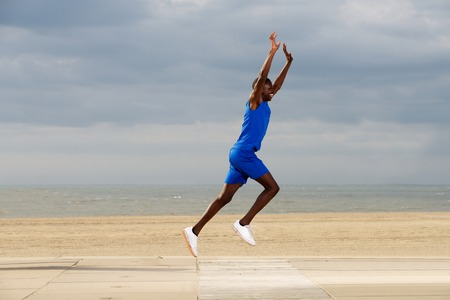 adult hand: Full body side portrait of fit young african american man jogging at beach with arms raised Stock Photo