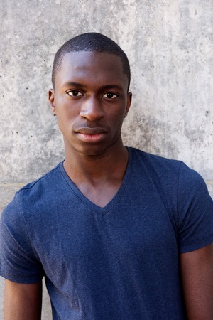 black guy: Close up portrait of handsome young black guy standing agaisnt gray wall Stock Photo