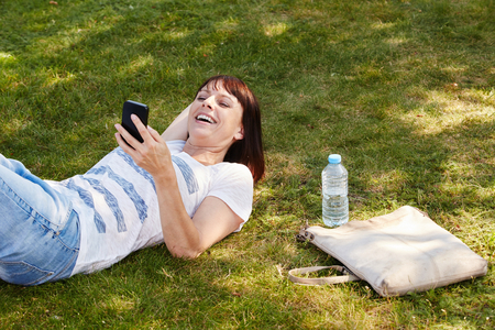 Portrait of beautiful woman lying in grass smiling with smart phone Stock Photo