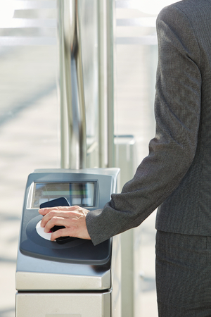 validating: Rear portrait of woman walking through turnstile with pass
