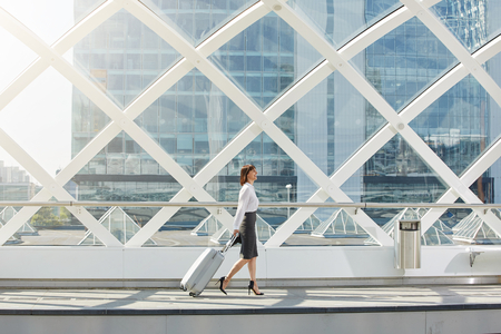 Full length side portrait of traveling business woman walking with suitcase in terminal