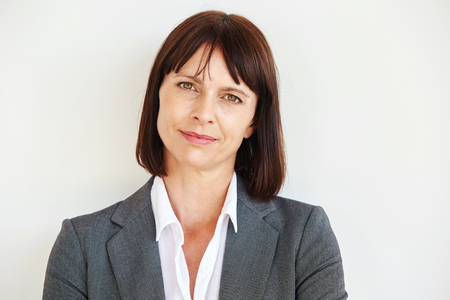 Close up portrait of serious business woman standing by white wall Foto de archivo