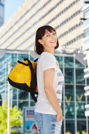 Portrait of happy older woman carrying duffel bag in city