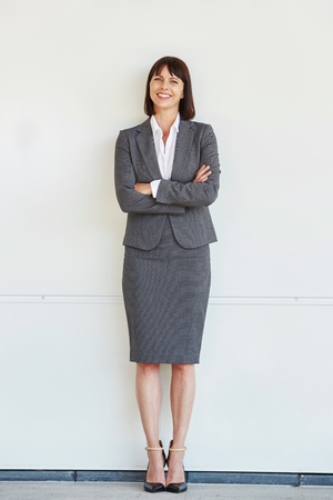 Full body portrait of professional business woman standing with arms crossed by white wall Foto de archivo