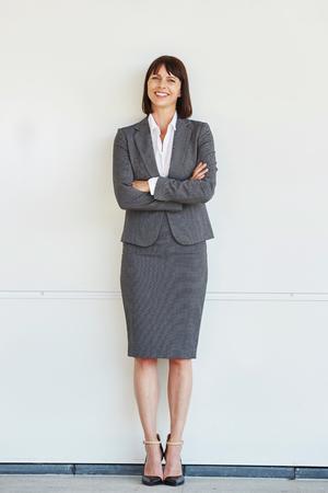 Retrato de cuerpo entero de la mujer de negocios profesional de pie con los brazos cruzados por la pared blanca