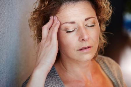 Close-up portret van oudere vrouw met de hand aan het hoofd van de pijn