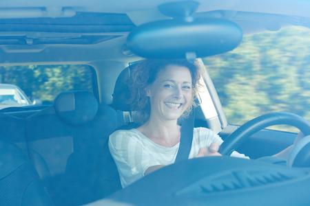 commute: Portrait of smiling older woman in car on commute Stock Photo