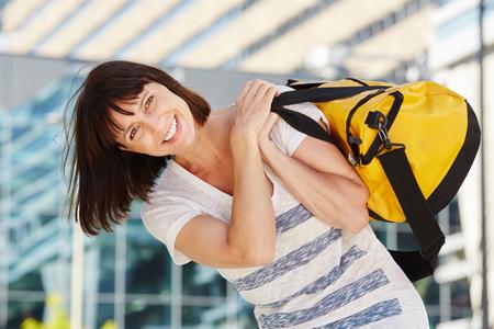 shoulder carrying: Portrait of happy traveler carrying duffel bag over shoulder