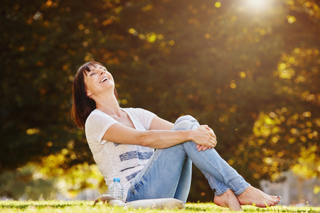 Full body portrait of happy barefoot woman sitting on grass in park Stock Photo