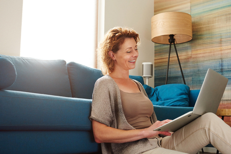 Side portrait of woman sitting on floor in apartment with computer