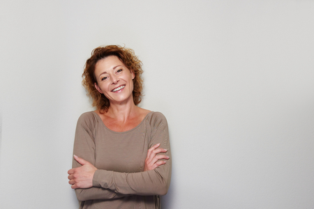 Close up portrait of smiling woman standing with arms crossed against white wall