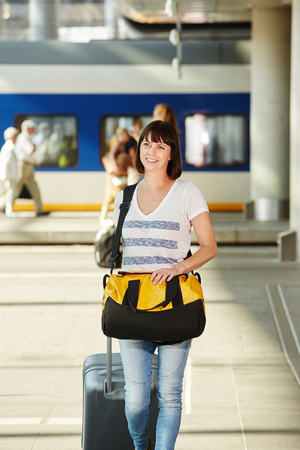 Portrait of older female traveler with duffel bag and suitcase at train station Stock fotó