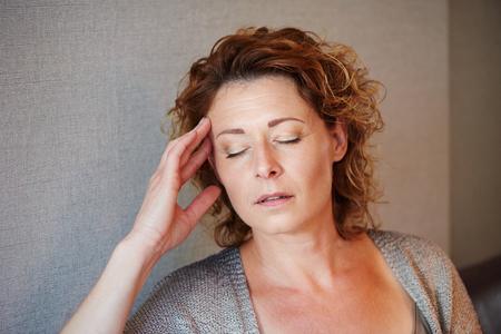 Close-up portret van vrouw van middelbare leeftijd met een hand aan het hoofd van de pijn