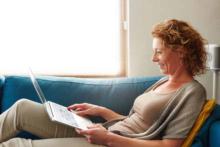 Side portrait of woman lying on sofa with laptop smiling