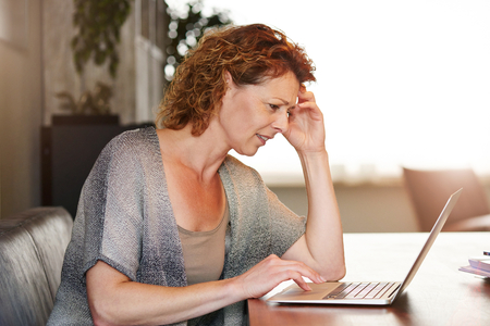 Portrait of woman looking at computer thinking sitting at table