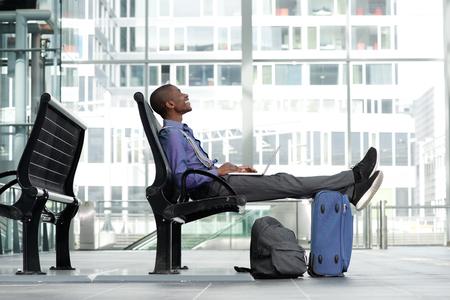 Zij portret van lachende jonge zakenman met laptop en bagage op de luchthaven Stockfoto