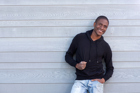 cool guy: Portrait of a cool young black guy smiling with black sweatshirt Stock Photo