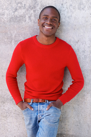 cool guy: Portrait of cool smiling african american guy standing against wall