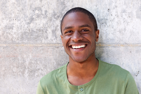 Close up portrait of cheerful young black man smiling against wall Foto de archivo