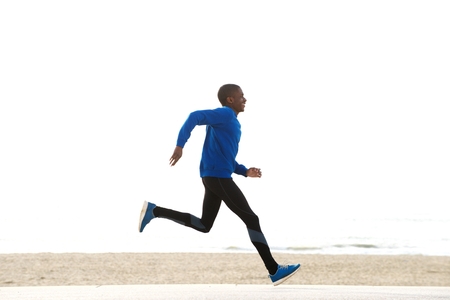 black male: Full length side portrait of young african american man running by the beach Stock Photo