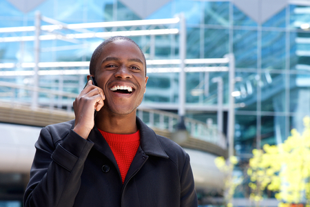 cool guy: Close up portrait of cool black guy laughing with mobile phone Stock Photo