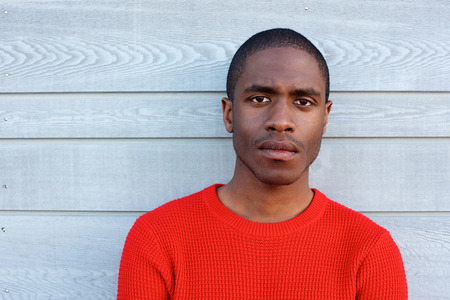 black guy: Close up portrait of serious black guy in red sweater Stock Photo