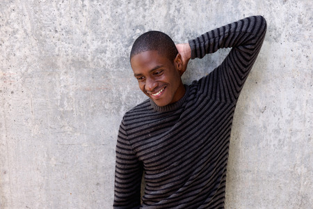 cool guy: Portrait of a cool young black guy smiling with hand behind head