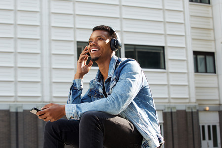 male face: Portrait of happy african american guy listening to music with cellphone