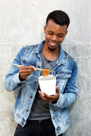 young male: Portrait of smiling young man standing with box of noodles and chopsticks