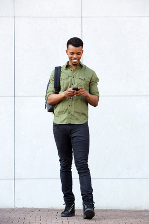 body bag: Full body portrait of handsome african man standing with smart phone and bag Stock Photo