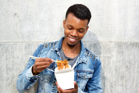 takeout: Close up portrait of smiling handsome man enjoying takeout noodles